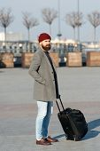 Man Bearded Hipster Travel With Big Luggage Bag On Wheels. Let Travel Begin. Traveler With Suitcase  poster