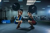 Two male weightlifters doing squats with barbells poster