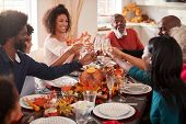 Multi generation mixed race family raise their glasses to make a toast at their Thanksgiving dinner  poster