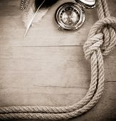ship ropes and compass with feather on wood background board