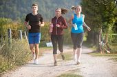 group of young people jogging on country road runners running on open road on a summer day poster