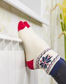 Womens Feet In Socks Are Heated On The Radiator Of Water Heating In The Room. poster