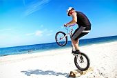 A teenager with bike making a trick on a beach