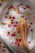 Top view of beautiful woman relaxing in bath with foam and rose petal
