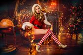 Sexy Santa girl in red body suit and striped stockings poses in luxurious apartments decorated Chris poster