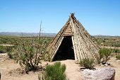 picture of teepee  - A native American Indian teepee made of wood sitting in the desert - JPG