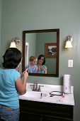 Big And Little Girls Playing With Makeup In The Mirror