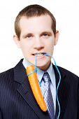 stock photo of dangling a carrot  - Handsome young business person dangling a carrot on a string from his mouth concpetual of offering an incentive bonus as a reward for harder work - JPG