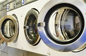 image of oversize load  - A row of industrial washing machines in a public laundromat - JPG