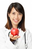 Asian female doctor holding red apple