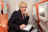 businesswoman posing with laptop on the board of plane in ecomomy class of aeroflot