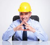 senior business man with helmet sitting at the desk with his hands together and smiling at the camera. on gray background
