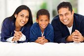 cheerful indian family lying on bed together