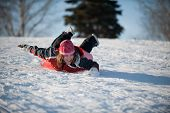 stock photo of toboggan  - a Girl sledding down the tobogganing hill - JPG