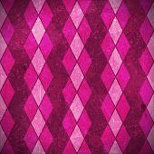 Geometric pattern made of rhombuses in various bright pink, purple, magenta colors overlaid with grunge elements and scratches to give it an aged and distressed feeling.