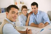 stock photo of draft  - Smiling financial adviser with young couple - JPG
