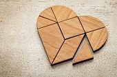 heart version of tangram, a traditional Chinese Puzzle Game made of different wood parts to build ab