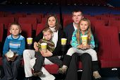 Young parents with three children watching a movie in the cinema