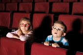 Little boy and girl watching a movie with interest in an empty cinema hall