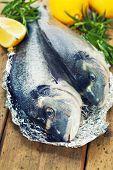 pescado fresco de la dorada con tomillo y limón en tablero de madera - comida y bebida