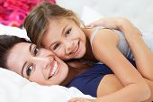 stock photo of snuggle  - Mother And Daughter Lying In Bed Together - JPG