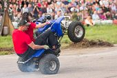 MOSCOW - AUG 25: Man with girl rides on the rear wheels on a quad bike on Festival of art and film s