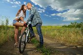 bike couple kissing in field