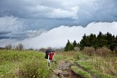 kid hiking with approaching storm