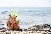 Hawaii girl swimming snorkeling with sea turtles. Happy woman on vacation with snorkel mask lying on