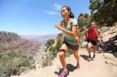Trail running cross-country runners in race on path in Grand Canyon, USA. Fit athletes jogging and t