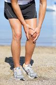 Running injury - Man out jogging with knee pain. Closed up veiw of the hands of a man out jogging on the beach clutching his knee as though in pain