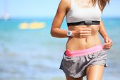Runner woman with heart rate monitor running on beach with watch and sports bra top. Beautiful fit female fitness model training and working out outside in summer at part of healthy lifestyle.