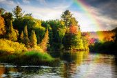 stock photo of rain  - A scenic lake or river during a light rain displaying a rainbow in the mist on an autumn day close to sunrise or sunset - JPG