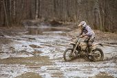 stock photo of motocross  - Motocross driver on wet and muddy terrain in Finland - JPG