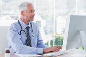 picture of antibiotics  - Doctor typing on his computer in the office - JPG