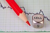 Financial Downtrend Chart,  Red Pencil And Dice Cube With The Word Selll. Selective Focus