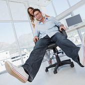 Smiling designers having fun with on a swivel chair in their office