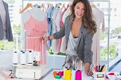 stock photo of self-employment  - Young fashion designer measuring dress on a mannequin and looking at the camera - JPG