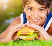 Closeup portrait of cute happy boy eating big tasty fatty burger outdoors, lying down on green field and enjoying sandwich with cheese, meat and vegetables in sunny day