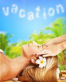Closeup atraente mulher deitada na mesa de massagem ao ar livre, flor de frangipani, no cabelo, antistr