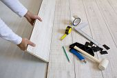 picture of laminate  - Worker laying a floor with laminated flooring boards - JPG