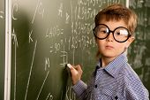 stock photo of schoolboys  - Portrait of a cute schoolboy in round glasses writing on a blackboard in a classroom - JPG