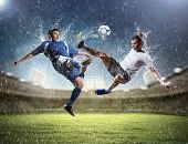 stock photo of wet feet  - two football players in jump to strike the ball at the stadium - JPG