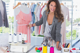 stock photo of dress mannequin  - Young fashion designer measuring dress on a mannequin and looking at the camera - JPG
