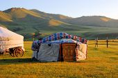 stock photo of yurt  - Traditional ger tent home of Mongolian nomads on the grass plains of the steppe with colorful rolling hills - JPG