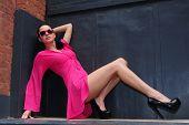 Attractive brunette model posing in pink dress