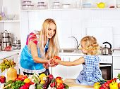 Mother and daughter prepare at kitchen.