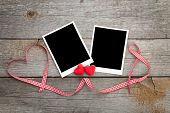 Two photo frames over wooden background with red ribbon and candy hearts