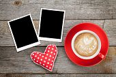 Two photo frames over wooden background with red coffee cup and heart toy