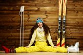 Happy woman with skis and ski boots sitting near wooden wall
